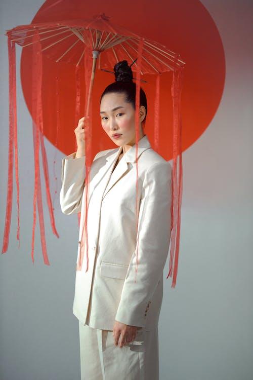 Woman in White Blazer Holding A Red Umbrella