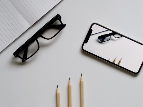 Three Pencils, Eyeglasses, and Smartphone on White Table
