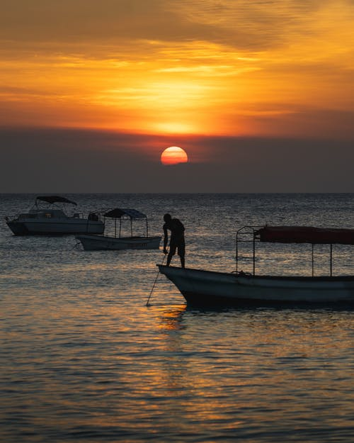 Fisherman Standing on a Boat at Sunset