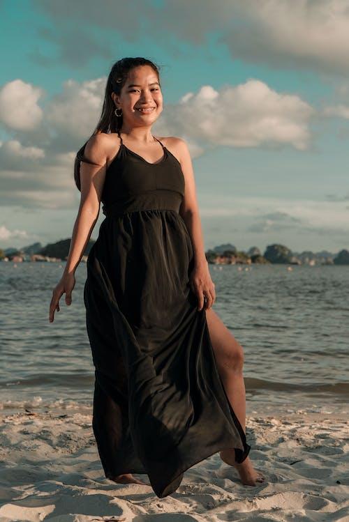 Woman in Black Spaghetti Strap Dress Standing on Beach