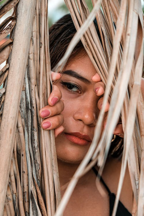 Womans Face on Brown Wooden Sticks