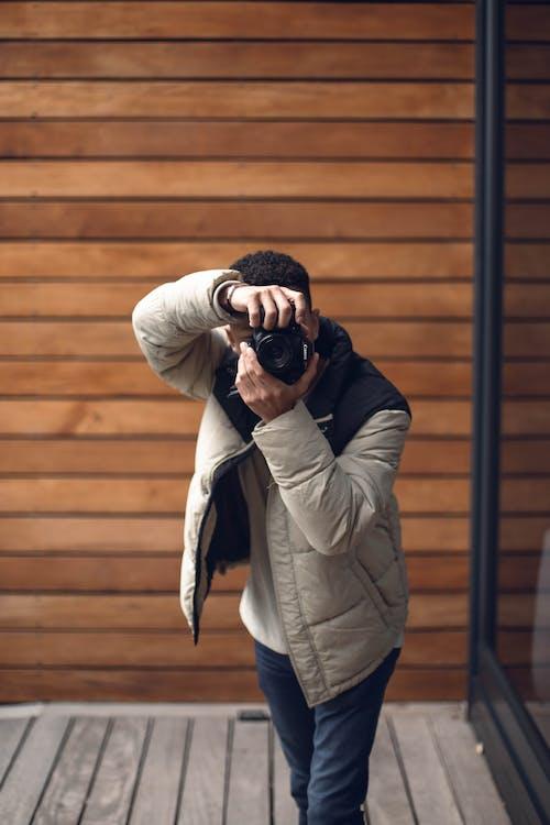 Man in White Jacket Taking Photo Using Black Dslr Camera