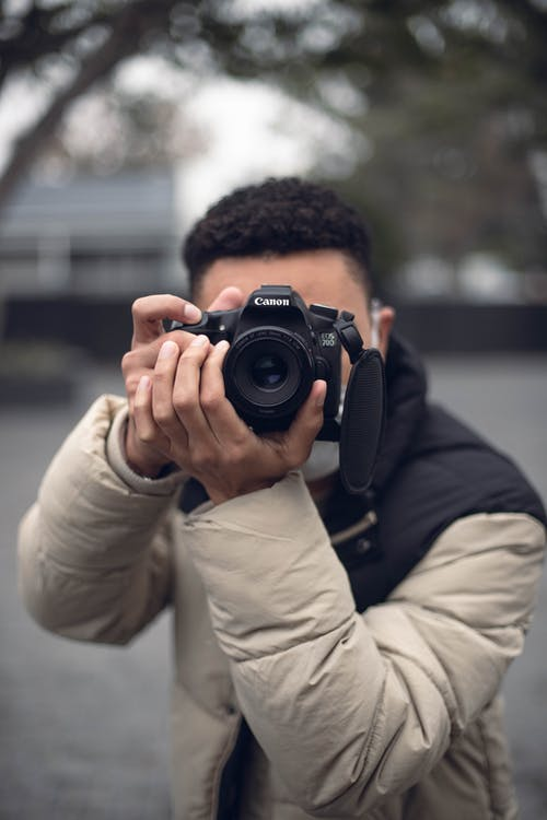 Close-Up Shot of a Male Photographer Taking Photos