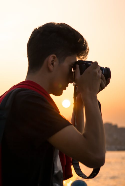 Close-Up Shot of a Male Photographer Taking Photos Using a DSLR Camera during Sunset