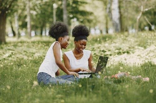 Two Afro-Haired Women Sitting on a Field while Using a Laptop