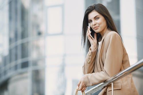 Woman in Beige Jacket Using Hand Phone