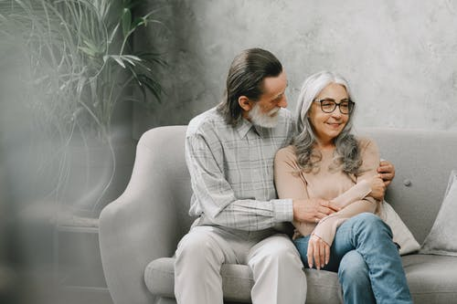 Man and Woman Sitting on Couch Embracing