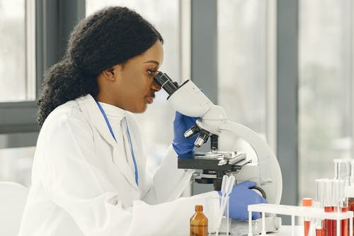 Woman Wearing a White Lab Coat Looking Through a Microscope