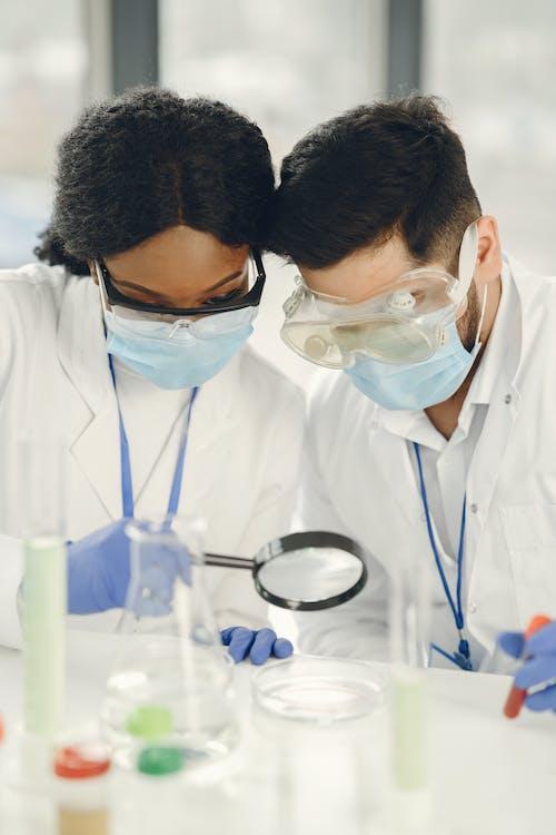 Man and Woman Looking at the Petri Dish Through Magnifying Glass