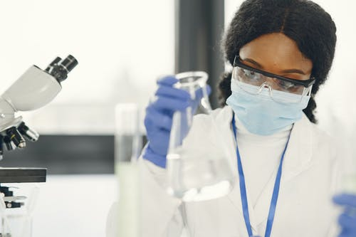 Woman Wearing Protective Goggles and Face Mask in the Laboratory