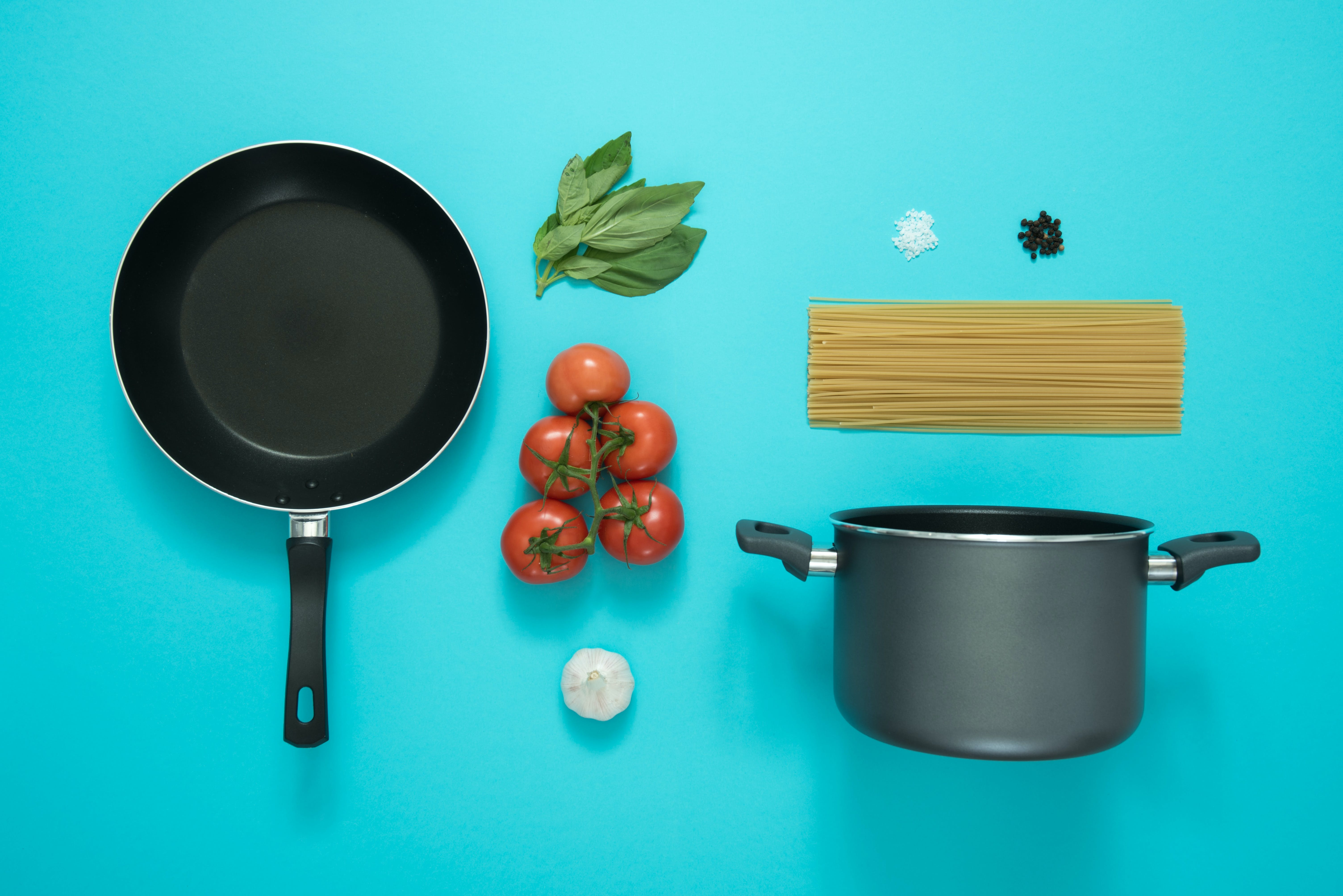 Black and Gray Cooking Pot and Frying Pan With Tomatoes