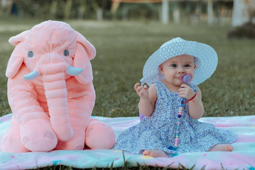 Cute Baby in Lavender Dress Sitting Next to an Elephant Toy