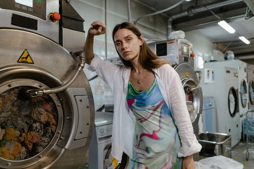 Woman in White Cardigan Standing Beside Stainless Steel Washer