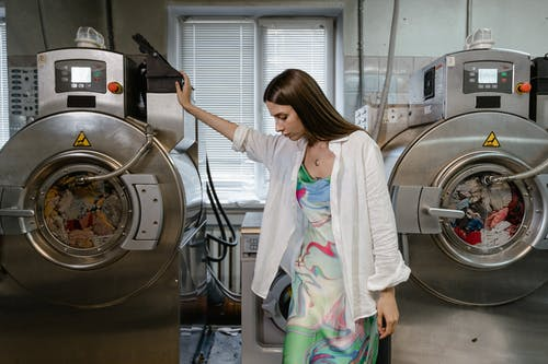 Woman in White Long Sleeve Shirt and Colorful Dress Standing Beside Stainless Steel Washing Machine