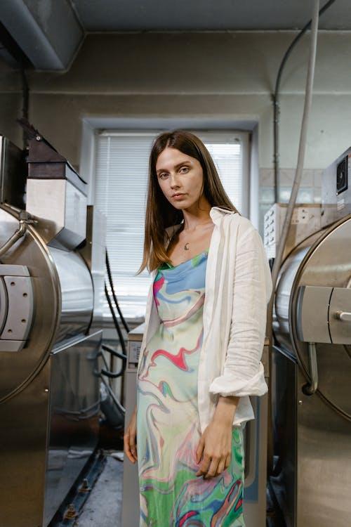 Woman in White Cardigan Standing Near Gray and Black Machine