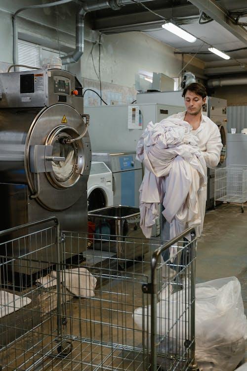 Man in White Robe Standing Beside Washing Machine