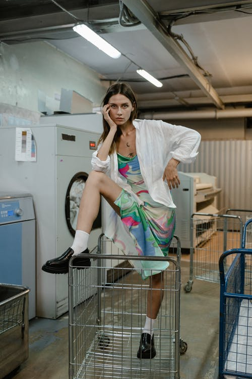 Woman in White Long Sleeve Shirt and Green Skirt Sitting on Gray Shopping Cart
