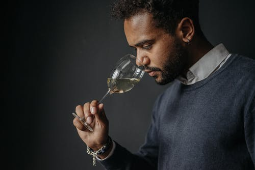 Man in Blue Sweater Holding Clear Wine Glass