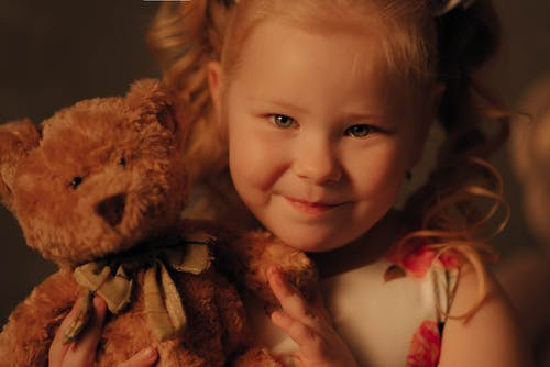 Close-Up Shot of a Cute Girl Holding a Stuffed Toy while Looking at Camera