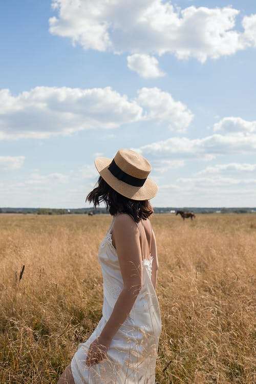 Woman in White Dress Standing on Brown Grass Field
