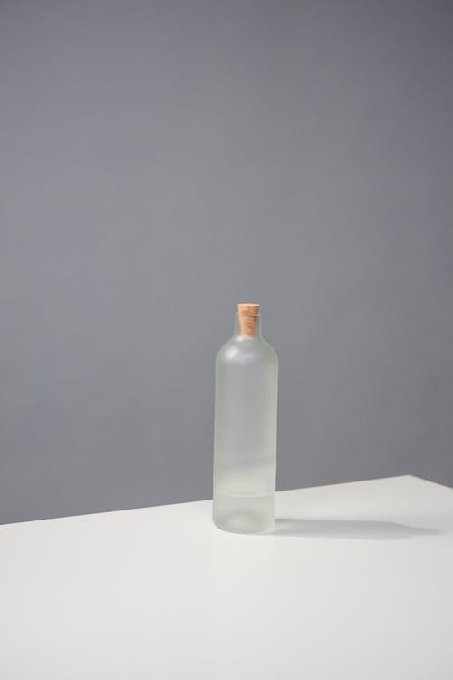 White Glass Bottle on White Table