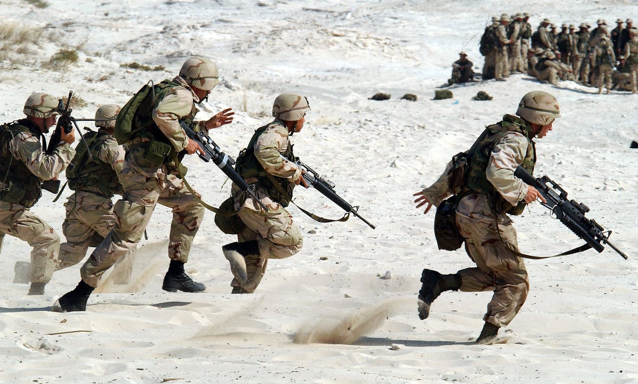 5 Soldiers Holding Rifle Running on White Sand during Daytime