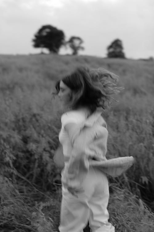 Grayscale Photo of a Woman Running in a Field