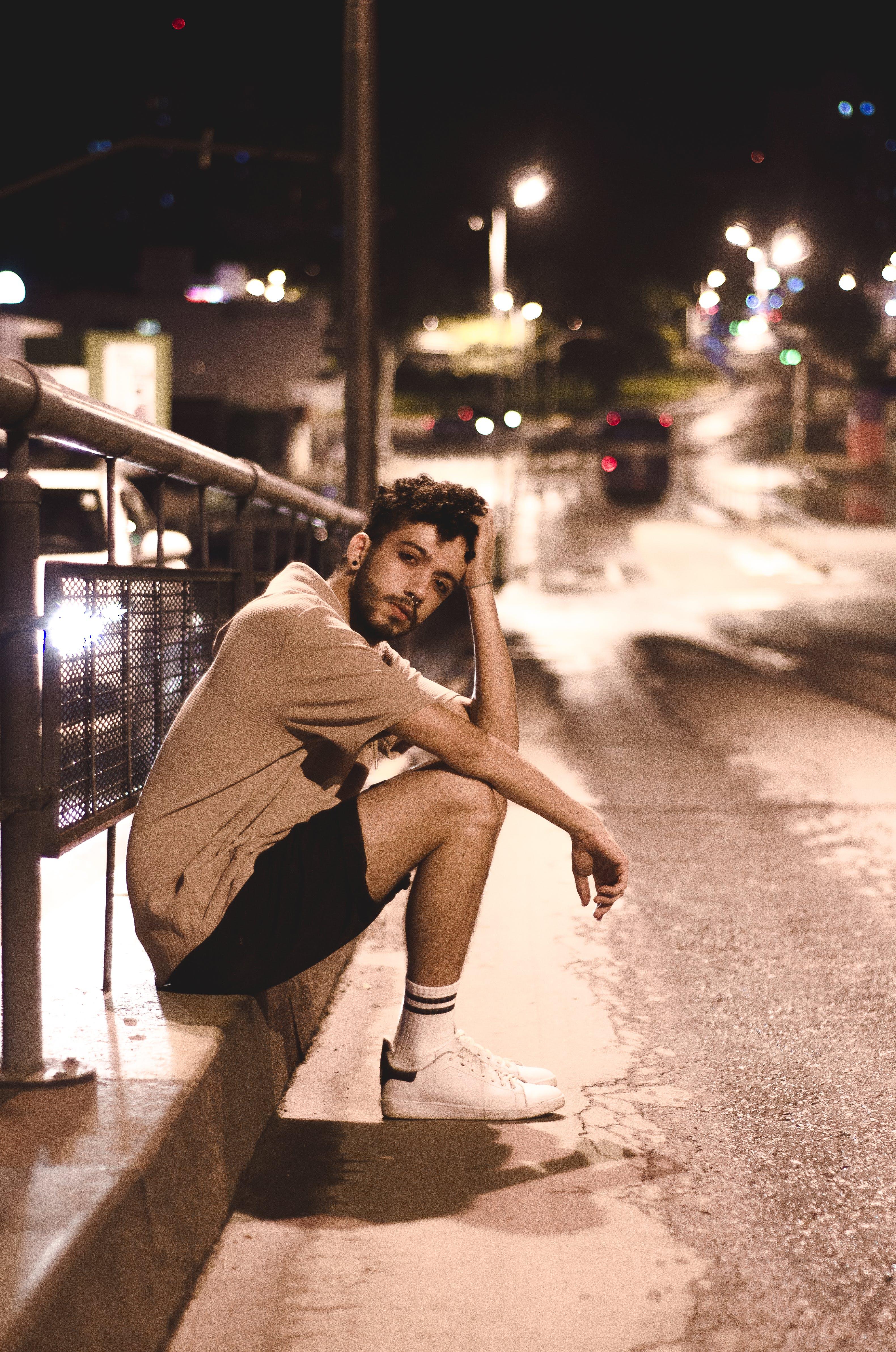 Man Wears Brown Shirt and Black Shorts Seats Beside Black Street Post