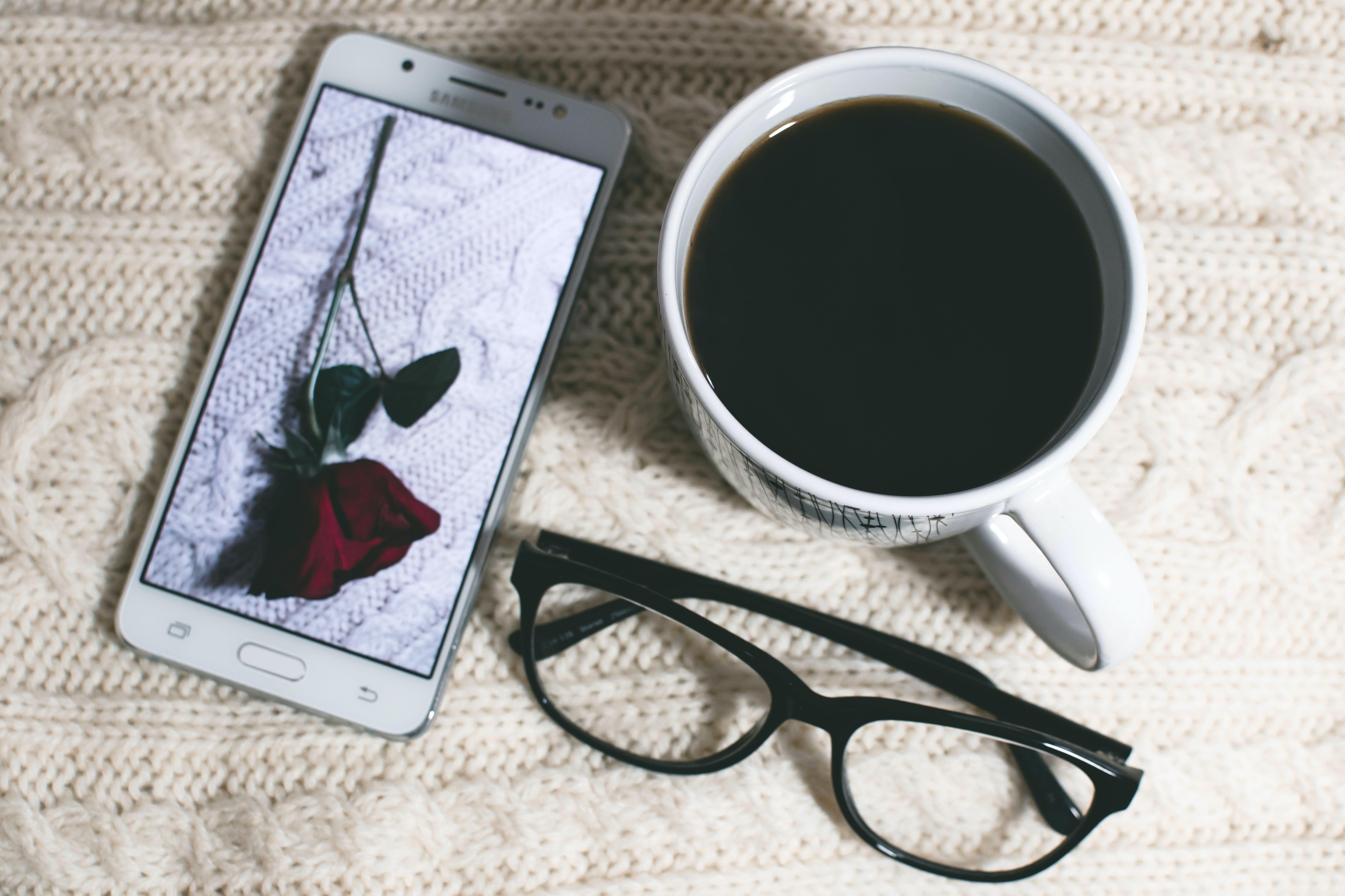 Phone Near Mug and Eyeglasses on Table