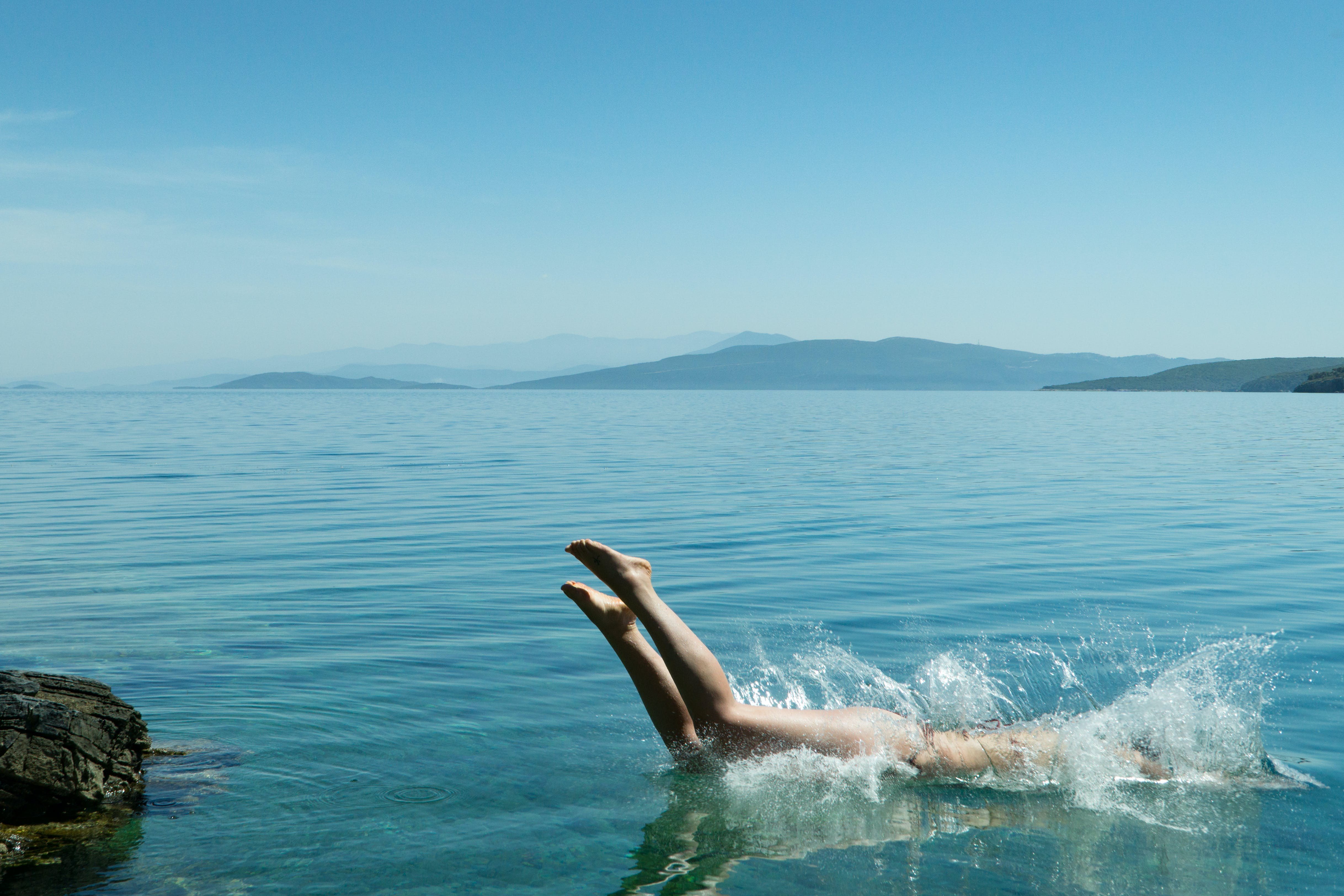 Person Diving on Body of Water during Daytime