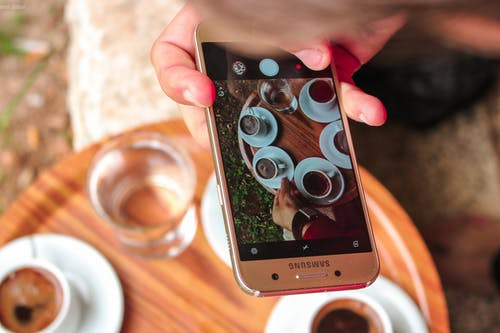 Person Holding a Samsung Galaxy Smartphone Taking a Picture on Their Coffees