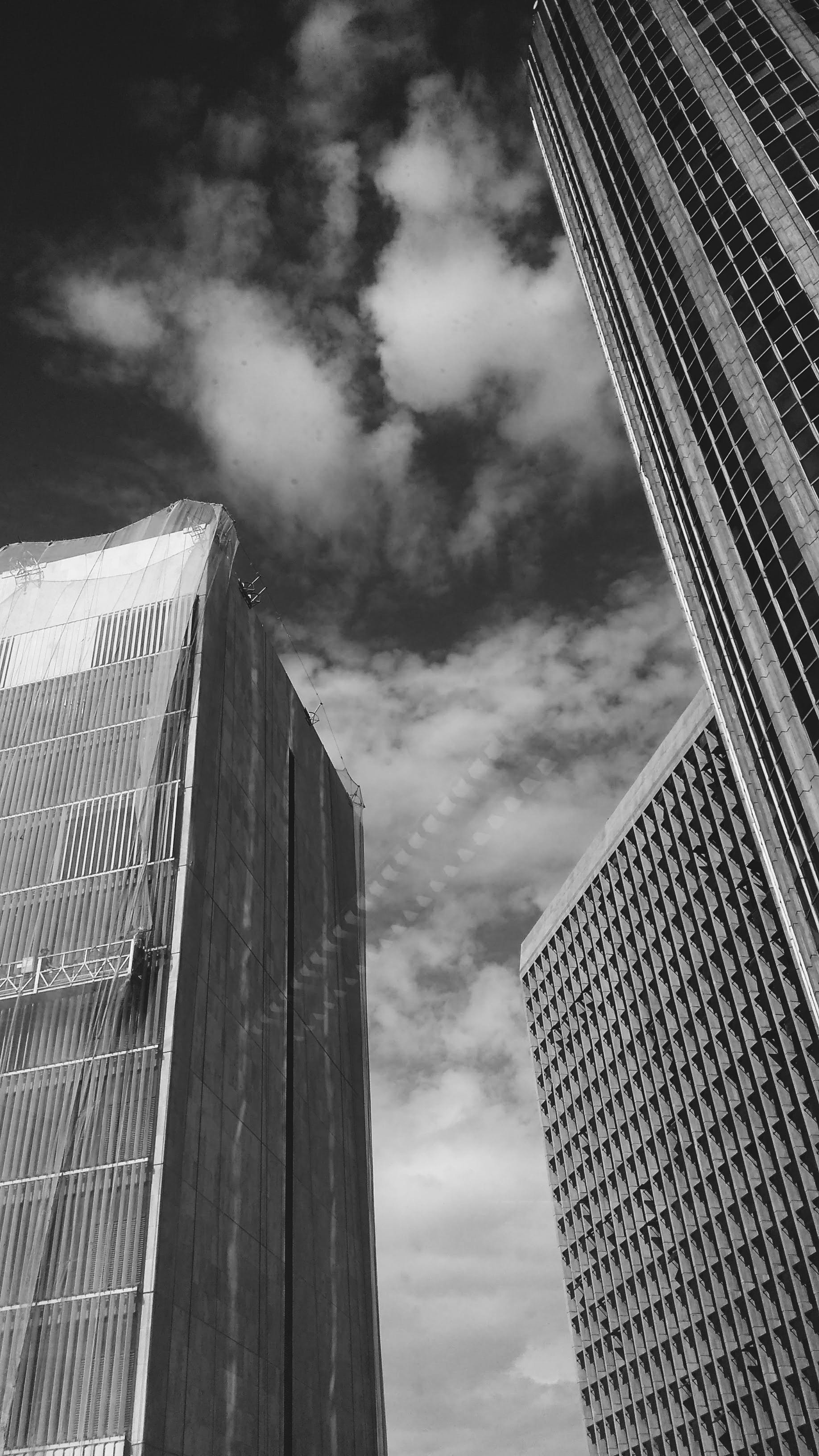Low Angle Grayscale Photography of Buildings and Clouds