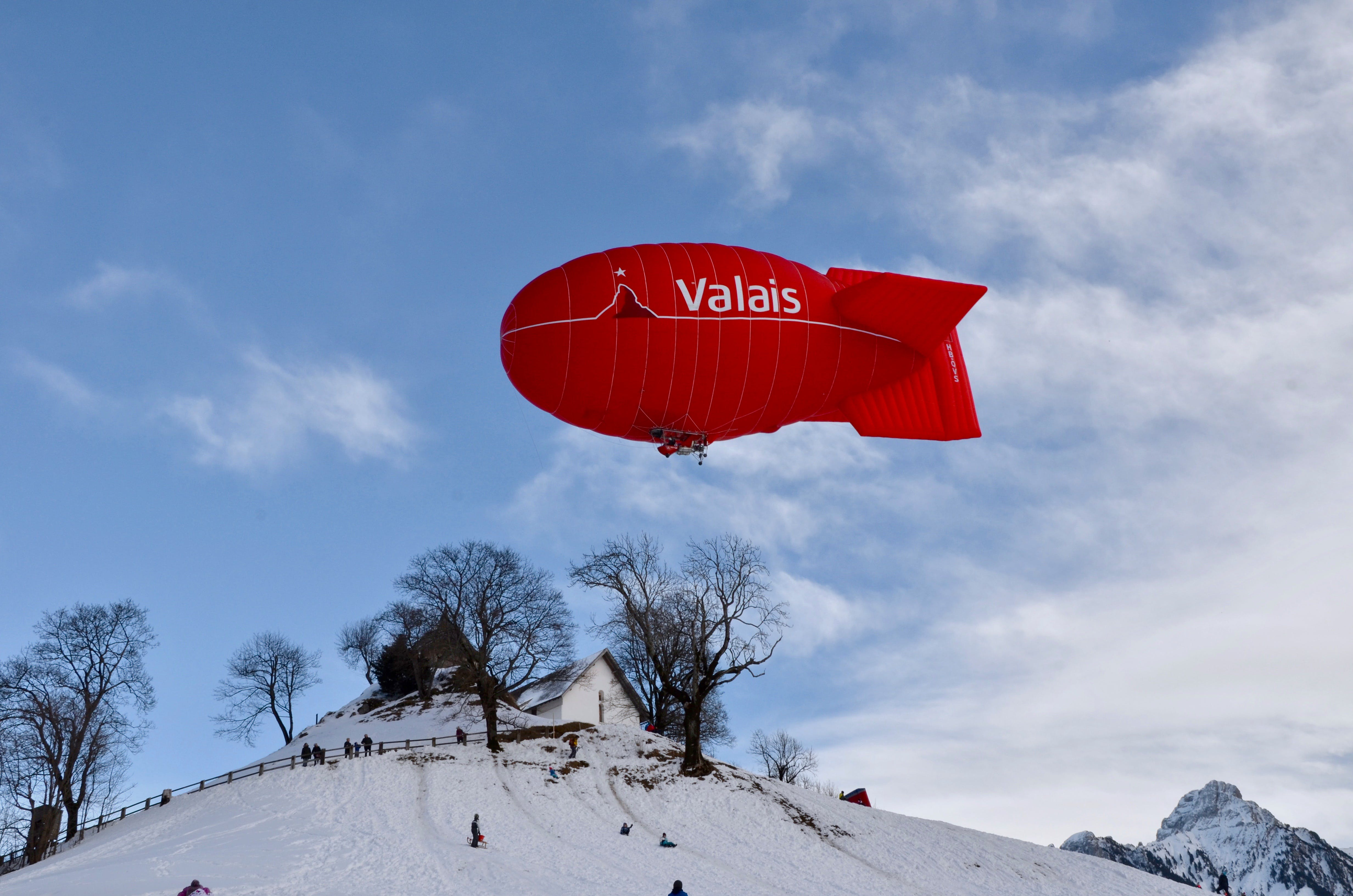 Red Valais Blimp Above White Wooden House