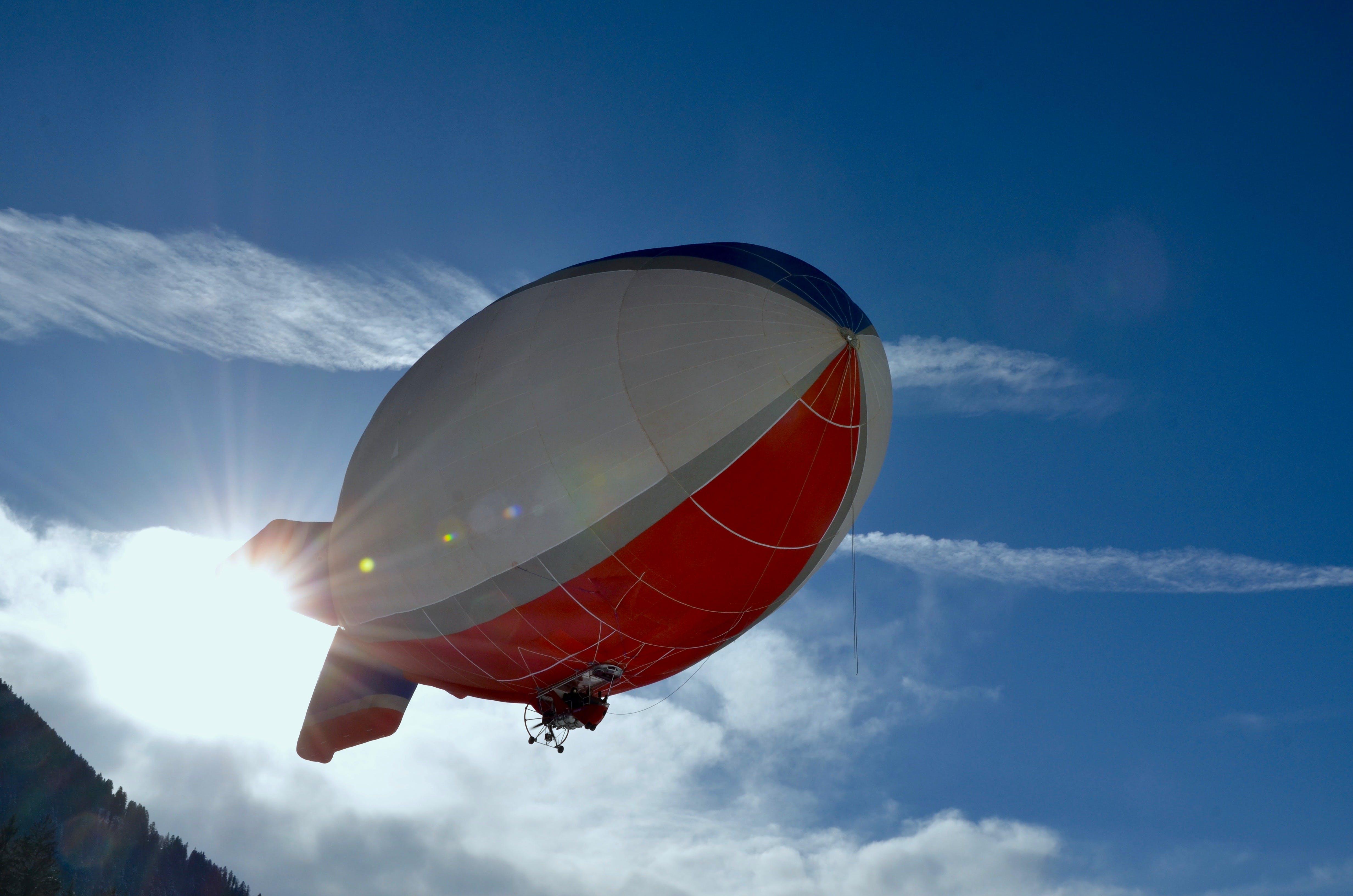 White and Red Blimp Flying