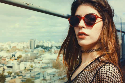 Woman Wearing Black Lace Scoop Neck Top and Red Framed Black Lens Sunglasses