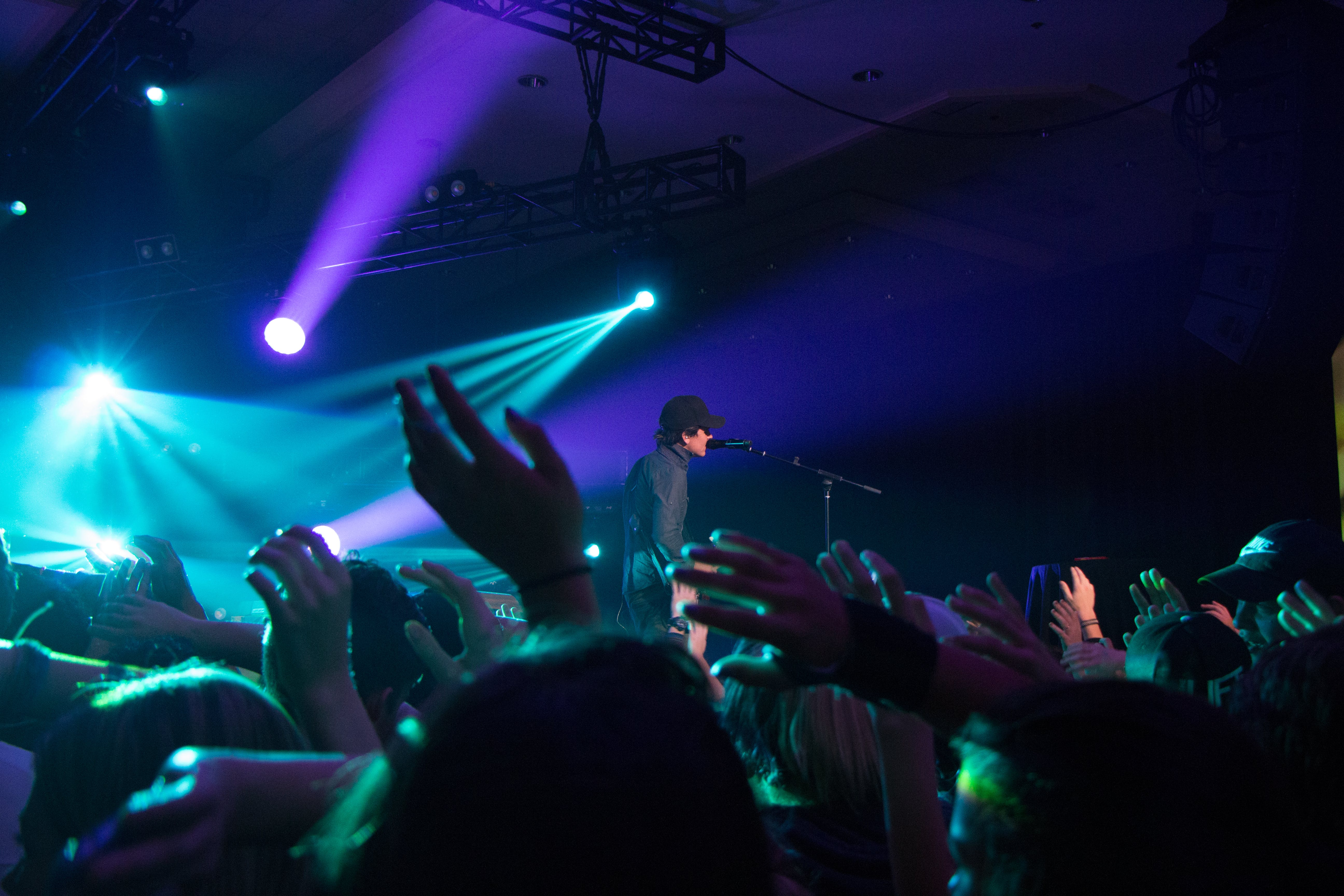 Man Singing on Stage With Stage Lights Near Crowd