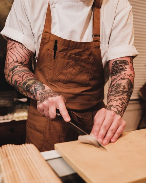 Person in Brown and White Apron Holding Black Pen