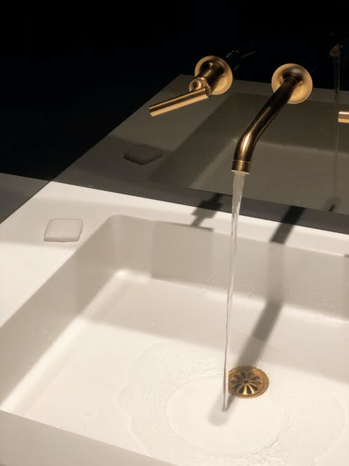 Water Flowing from Bronze Colored Faucet