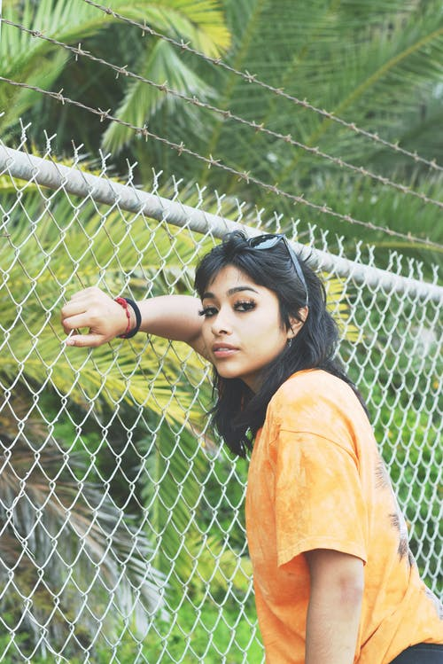 Side view of young ethnic female in t shirt leaning on metal fence while looking at camera against palm foliage