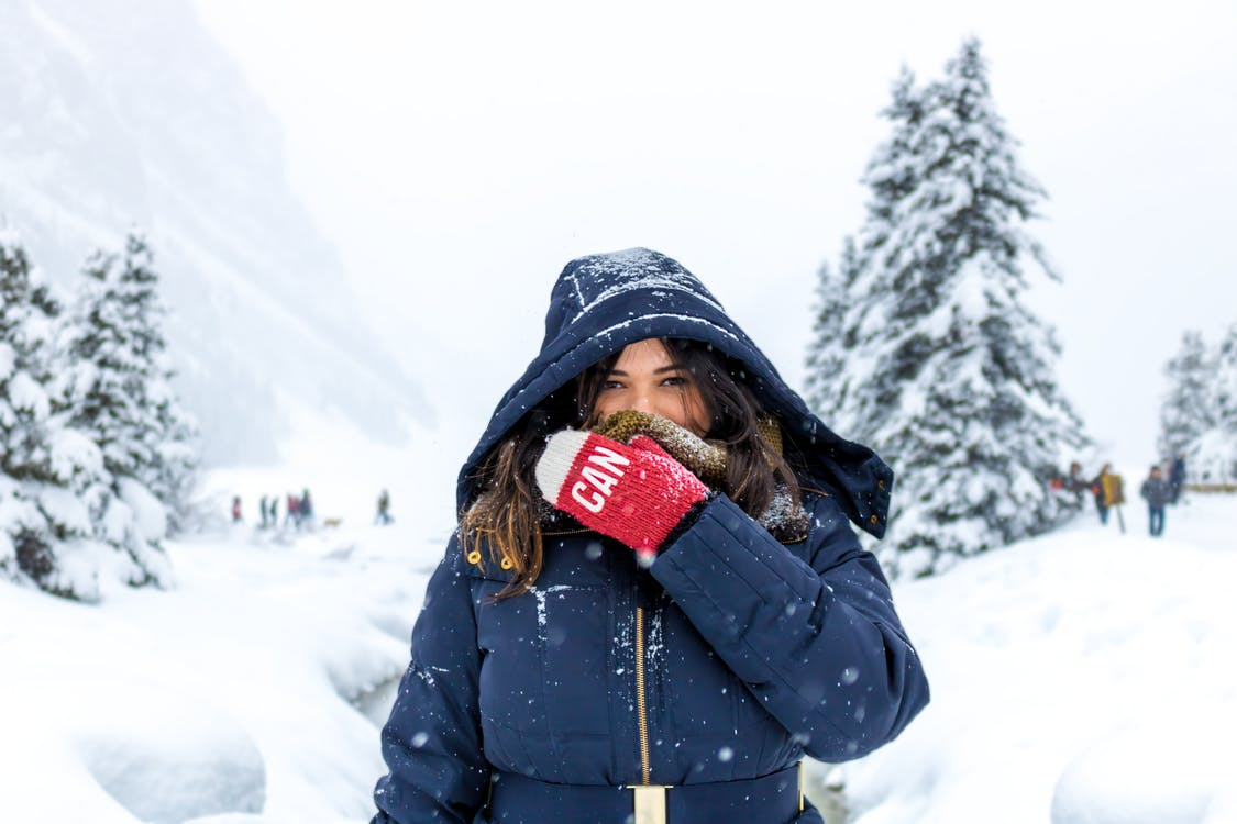 Woman in Blue Zip-up Hooded Jacket Standing on Snow