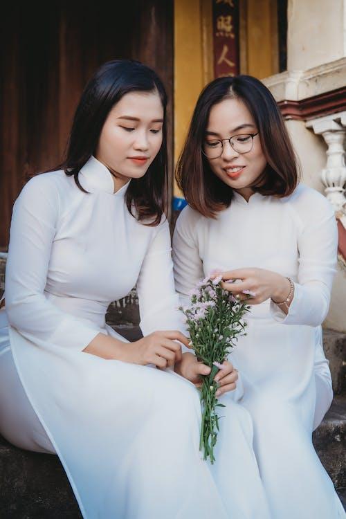 2 Women in White Long Sleeve Dress Holding Green Plant