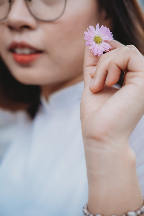 Woman in White Shirt Holding Purple Flower