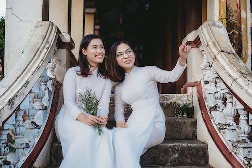 Woman in White Long Sleeve Dress Beside Woman in White Long Sleeve Dress