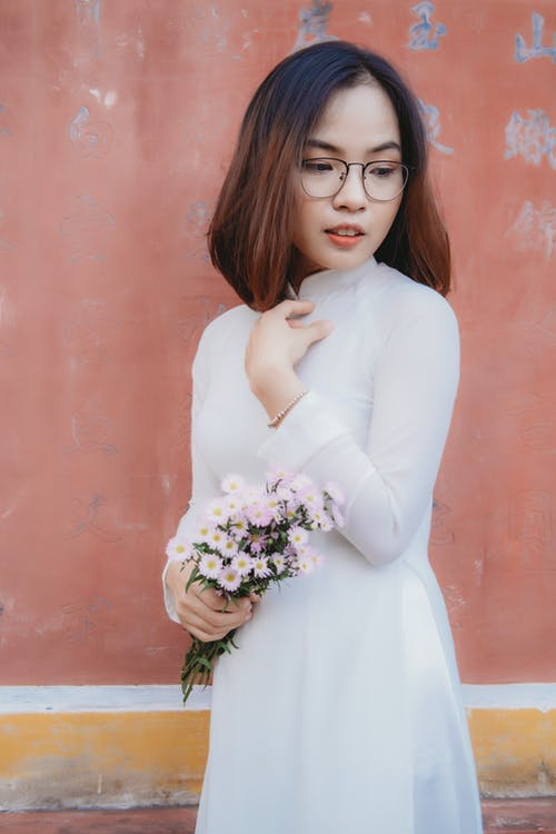 Woman in White Long Sleeve Shirt Holding White Flower Bouquet