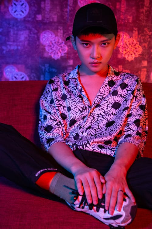 Man in Black White and Red Floral Button Up Shirt Sitting on Red Sofa