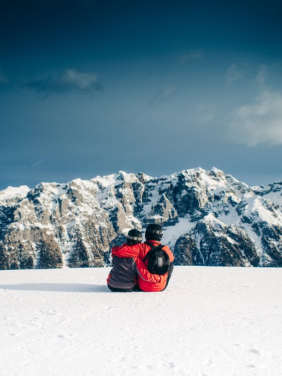 Two Person Sitting on White Snowfield