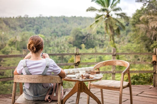 Brown-haired Woman Sitting on Brown Wooden Chair on Patio