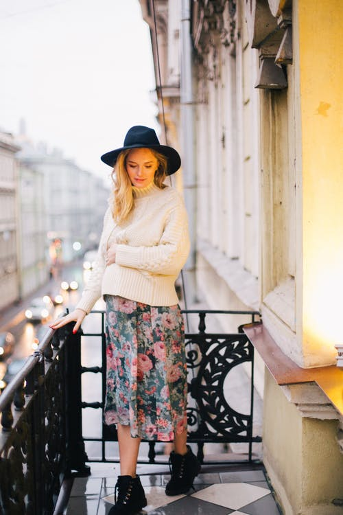 Pregnant Woman Wearing White Sweater and Multicolored Floral Skirt Standing on Balcony