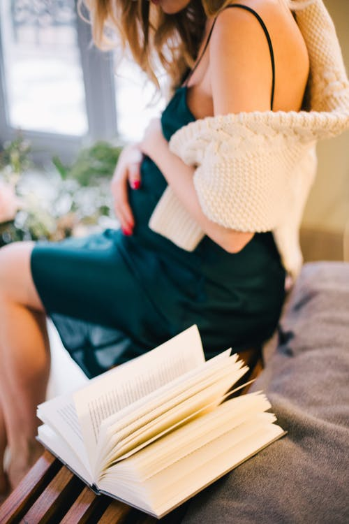 Selective Focus of Pregnant Woman in Black Spaghetti Strap Dress Sitting on Chair Beside Opened Book