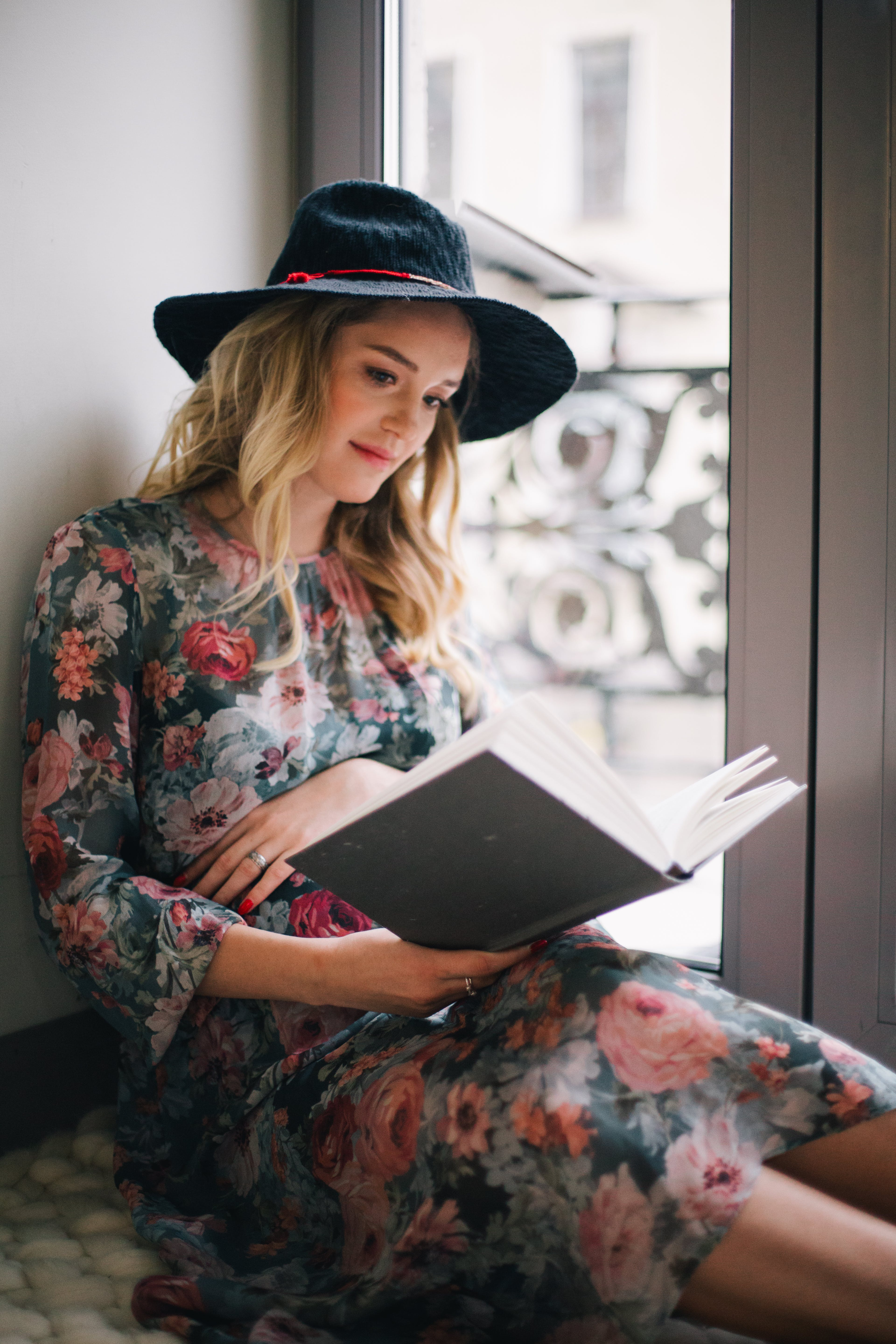 Pregnant Woman Wearing Green, Red, and White Floral Dress Reading a Book Near Window